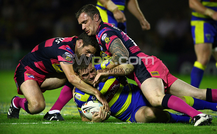 PICTURE BY VAUGHN RIDLEY/SWPIX.COM...Rugby League - Super League Playoffs - Warrington Wolves v Leeds Rhinos - Halliwell Jones Stadium, Warrington, England - 30/09/11...Warrington's Simon Grix is tackled by Leeds Danny Buderus and Jamie Peacock.  Grix receives a gash to his upper right eye.
