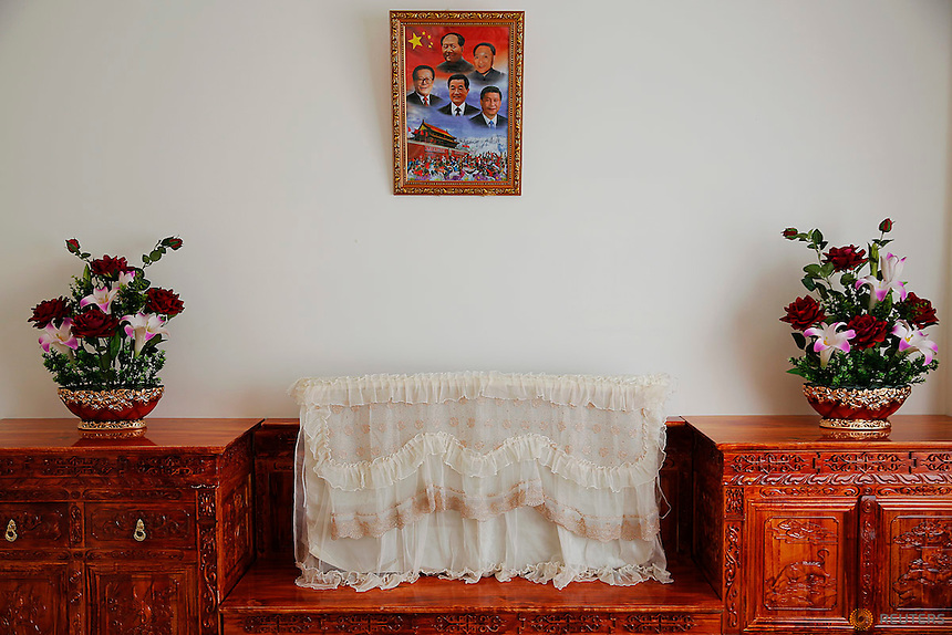 A picture of former and present Chinese leader hangs over a covered TV set and some plastic flowers decorating a room for orphans at a newly built Lhasa Children Welfare House in Lhasa, Tibet Autonomous Region, China November 19, 2015. REUTERS/Damir Sagolj