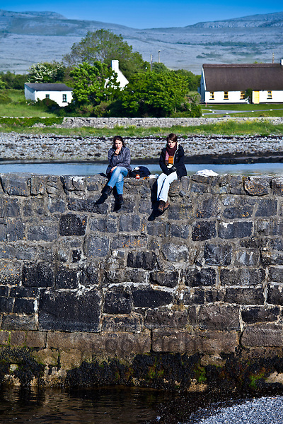Tourists taking a lunch break on the pier sea defence wall at Ballyvaughan, County Clare, West Coast of Ireland