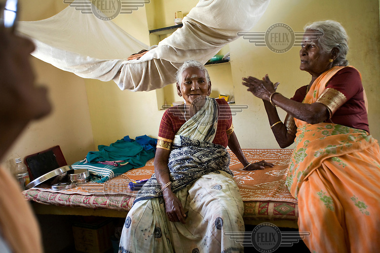 Amaravathy and Jayamal talk to their friends inside their cottage in the Tamaraikulum Elders' village. The village is a pioneering experiment initially set up by HelpAge India after the Asian Tsunami to help elderly people displaced by the natural disaster. Today, the village is a self-sustaining community providing a family environment where more able-bodied residents assist the less able-bodied and provides 100 older people with a safe place to live, free healthcare, emotional security, a good diet and professional care and support...