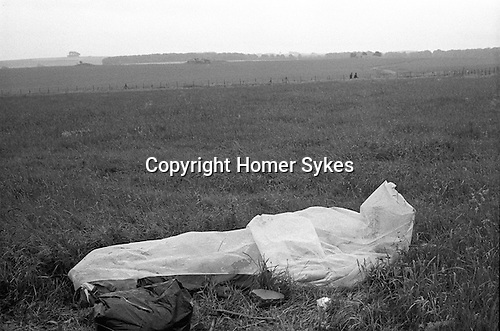 Free festival Stonehenge. Summer solstice 1976. Summer rain, hippy sleeps in a make shift  waterproof sleeping bag...