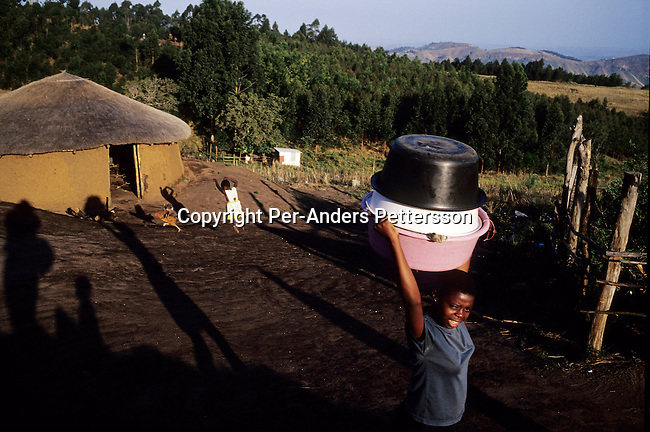 NGUDWINI, SOUTH AFRICA - SEPTEMBER 10: Nobule Ngema, age 16, walks to a nearby river to wash clothes as she's preparing to travel to the annual Reed Dance on September 10, 2004 in Ngudwini village in rural Natal, South Africa. Nobuhle is traveling on a bus and about 20.000 fellow maidens from all over South Africa is coming to dance for Zulu King Goodwill Zwelethini at the Enyokeni Royal Palace in Kwa-Nongoma about 350 kilometers from Durban. The girls come to the kingdom to declare their virginity and the ceremony encourages girls and young women to abstain from sexual activity to curb the spread of HIV-Aids. Its Nobuhle's first trip and she's already has three virginity certificates as she was tested in the village for the last three years. .(Photo: Per-Anders Pettersson).
