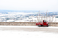 Red 'Ape' vehicle on the road to Trevi, in the snow covered Spoleto Valley, Umbria, Italy
