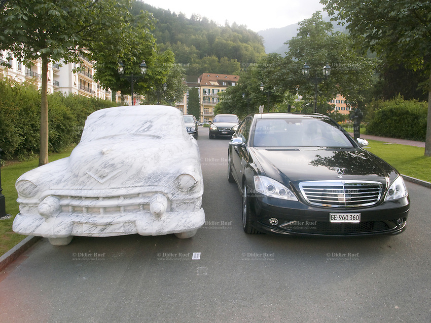 "Switzerland. Canton St. Gallen. Bad Ragaz. Two cars are are parked on the road: a classic american marble car and a new black luxury vehicle, a Mercedes S600. The marble car is an art piece, exhibited during the 4th Swiss Triennial Festival of Sculpture, called Bad RagARTz, an international cultural event with over 400 sculptures, which makes this outdoor show one of the largest of its kind in Europe. The marble was quarried in Carrara, a city and comune in the province of Massa-Carrara (Tuscany, Italy), famous its white or blue-gray marble. Both cars are parked in front of The Grand Hotel Quellenhof & Spa Suites, which is a member of the international hotel association ""The Leading Hotels of the World""  and ""Swiss Deluxe Hotels"".29.06.09  © 2009 Didier Ruef"