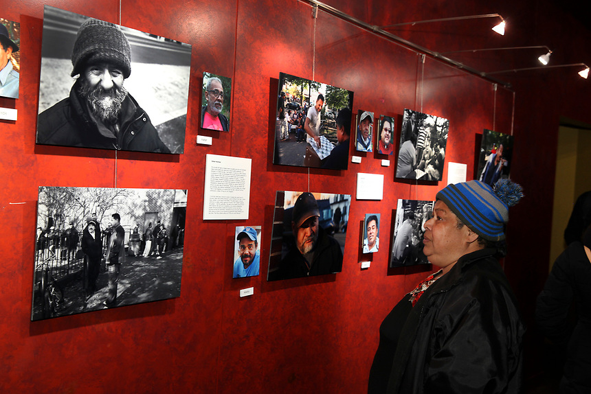 (180314RREI7972) About 200 people attended the opening of La Esquina - The Corner exhibition at Gala Theatre. The documentary project La Esquina revolves around the history of the Latinos at the corner of Mt. Pleasant St. and Kenyon St. NW. Maribel, one of the esquineros looks at the exhibition. Washington DC March 14, 2018 . ©  Rick Reinhard  2018     email   rick@rickreinhard.com