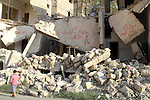 A Syrian boy walks past the rubble of buildings which destroyed by forces of Syria's President Bashar al-Assad, in a rebel-controlled area in the northern Syrian city of Aleppo, on August 31, 2015. Photo by Ameer al-Halbi
