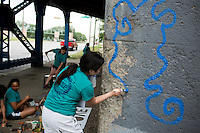 "Ali Grotkowski paints a mural under a train bridge during ""Circle the City with Service,"" the Kiwanis Circle K International's 2015 Large Scale Service Project, on Wednesday, June 24, 2015, in Indianapolis. (Photo by James Brosher)"