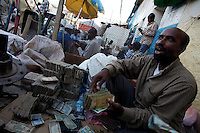 a man exchanges foreign currencies for Somali shillings  In Somaliland's Capital Hargeysa main exchange market on friday October the 19th 2007.///..Though not internationally recognized, Somaliland has a working political system, government institutions, a police force and its own currency. The territory has worked hard to win support for its claims to be a sovereign state. The former British protectorate has also escaped much of the chaos and violence that plague the rest of Somalia, although frequent clashes at the boarder with Puntland have created many problems recently. Poverty and unemployment are widely spread. the economy is highly dependent on money sent home by the diaspora..
