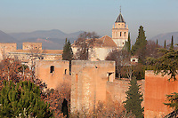 Walls and Southern towers of the Alhambra with the alcazaba or defensive fortress on the left, and the Palace of Charles V in the background, built by Pedro Machuca in the 16th century, Alhambra Palace, Granada, Andalusia, Southern Spain. The Alhambra was begun in the 11th century as a castle, and in the 13th and 14th centuries served as the royal palace of the Nasrid sultans. The huge complex contains the Alcazaba, Nasrid palaces, gardens and Generalife. Granada was listed as a UNESCO World Heritage Site in 1984. Picture by Manuel Cohen