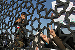 A Palestinian boy looks through the gate of Rafah border crossing during a rally calling on Egyptian authorities to open the crossing, in Rafah in the southern Gaza Strip December 22, 2015. Egypt has kept its Rafah crossing largely shut since Cairo's Islamist president was toppled by the army in 2013. Since then, it opened the crossing partially and on a few occasions to allow thousands of Palestinians to travel in and out of the Gaza Strip, border officials said. Photo by Abed Rahim Khatib