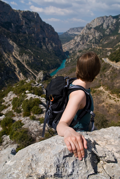Young adult female hiker with hand on rock enjoys view of gorge du Verdon, France