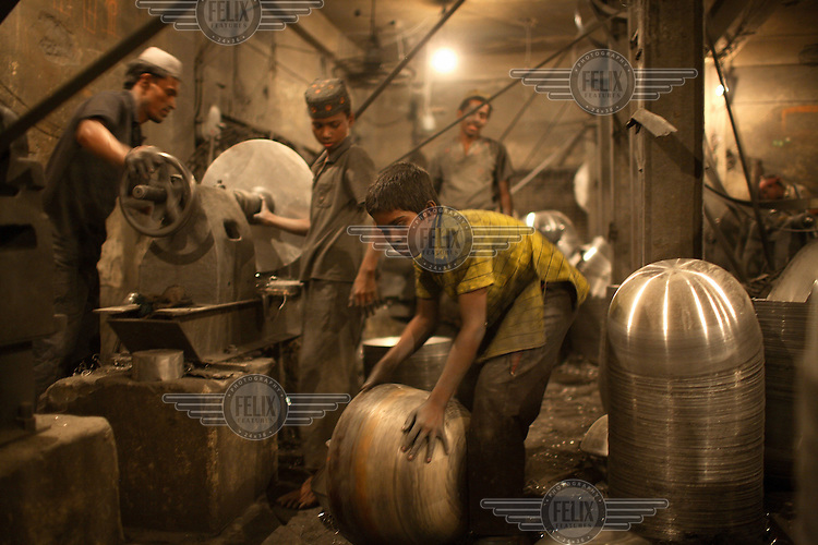 Children working in a silver cooking pot factory in Dhaka. It is common in Bangladesh for children of poor parents to work in various hazardous and labour-intensive workplaces to support their families. 17.5 percent of all children aged between 5-15 are engaged in economic activities. The average child labourer earns between 400 to 700 taka (1 USD = 70 taka) per month, while an adult worker earns up to 5,000 taka per month.
