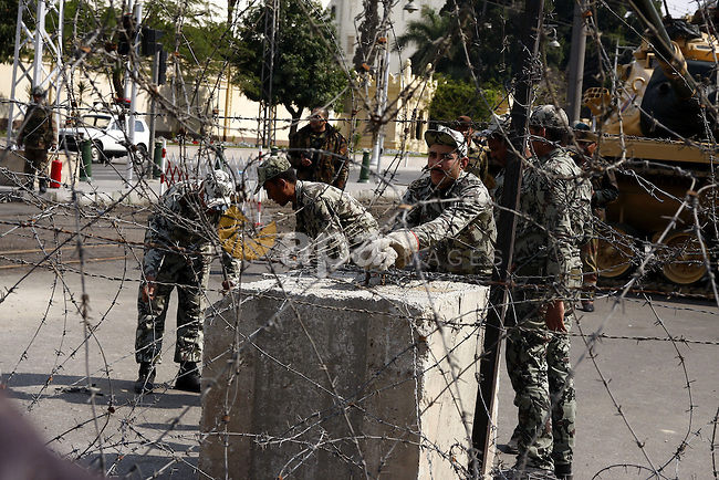 Egyptian Presidential guards block the entrence to Ettehadyya Presidential palace with barbed wire as Egyptian anti-government protesters march in Cairo, Egypt, Friday, Feb. 11, 2011. Egypt's military seemed to throw its weight Friday behind President Hosni Mubarak's plan to stay in office until September elections while protesters massed near the presidential palace in Cairo and other key symbols of the authoritarian regime in a new push to force the leader to step down immediately. Photo by Ahmed Asad