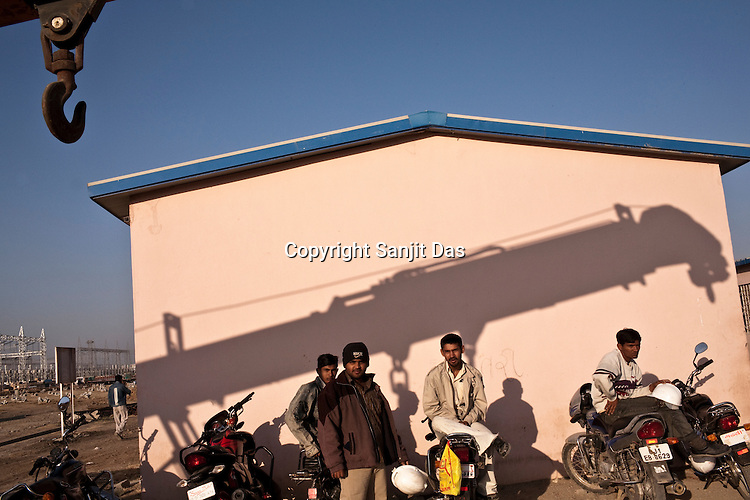 Indian workers are seen waiting outside the site office of the Adani Power plant in Mundra port industrial city of Gujarat, India. Indian power companies have handed out dozens of major contracts to Chinese firms since 2008. Adani Power Ltd have built elaborate Chinatowns to accommodate Chinese workers, complete with Chinese chefs, ping pong tables and Chinese television. Chinese companies now supply equipment for about 25% of the 80,000 megawatts in new capacity.