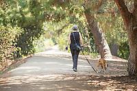 Woman Walking her Dog on Trail at Ralph B. Clark Regional Park in Buena Park