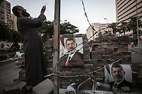 In this Sunday, Jul. 07, 2013 photo, a member of the Muslim Brotherhood salutes devoutly at one barricade set up in the streets nearby to the Republican Guard Headquarters during a rally in Cairo, Egypt. (Photo/Narciso Contreras).
