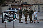 Israeli soldiers and a settler boy in a street of the Jewish Avraham Avinu settlement located in the Old City of Hebron. <br /> Hebron is a West Bank city that belongs to the Palestinian National Authority, about 400 Jewish settlers remain in some streets of the old town protected by some 2,000 Israeli soldiers.