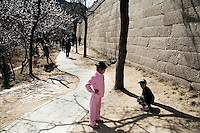 Tourists walk along a trail beneath the Great Wall at Badaling outside of Beijing, China.