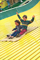 Brother and sister age 6 and 4 riding Giant slide at Minnesota State Fair.  St Paul  Minnesota USA
