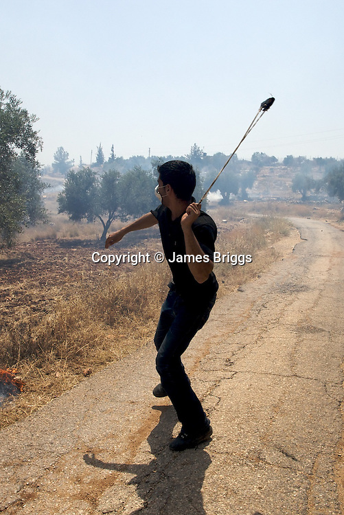 A shabab (Palestinian youth) uses a slinshot to throw rocks at IDF soldiers during a demonstration in the village of Bil'in near Ramallah on 04/06/2010.