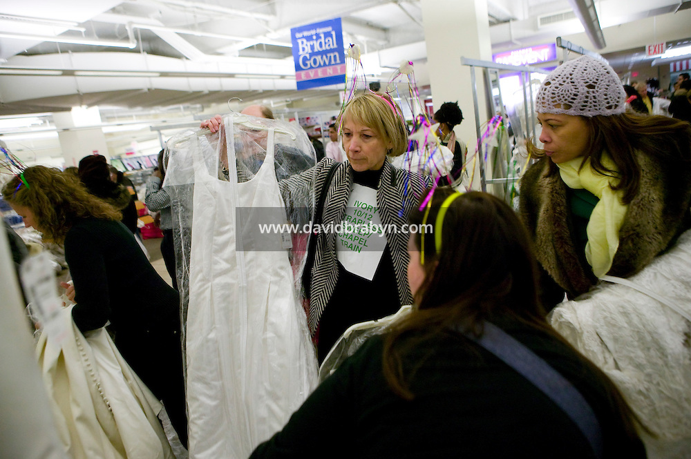 """Brides-to-be try on discounted wedding dresses with assistance from friends and family during the annual """"Running of the Brides"""", a a first-come-first-served bridal gown sale, at the Filene's Basement store in New York City, USA, 3 March 2006."""