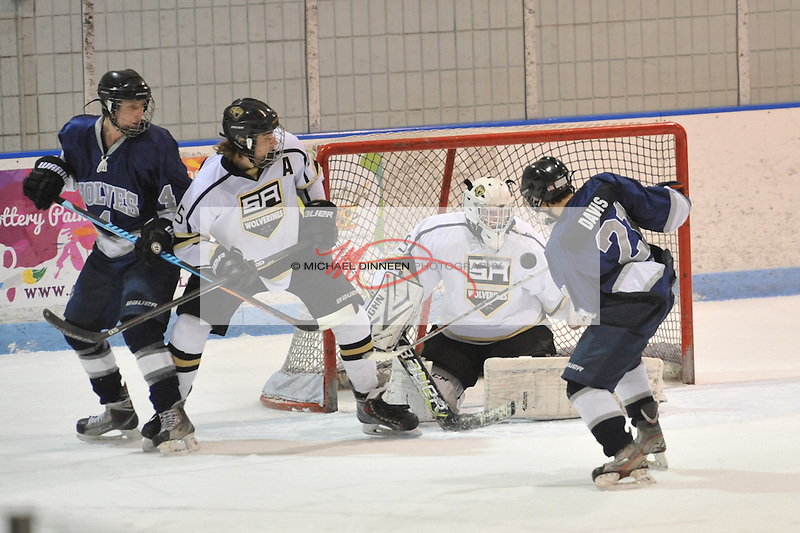 Eagle River's Schulyer Davis (21) puts a shot on Service goalie Max Irwin Wednesday, Jan. 6, 2016 at Ben Boeke Arena during the Wolves' 2-1 win. Looking on are Eagle River's Nat Nielsen (4) and Service's Jonah Hayes. Photo by Michael Dinneen for the Star