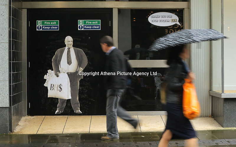 Pictured: Shoppers walk past a poster of Sir Philip Green on the door of the now closed down BHS store in Oxford Street, Swansea, Wales, UK. Tuesday 13 September 2016<br /> Re: Former owner of BHS, Sir Philip Green has paid a surprise 'visit' to the closed down BHS store in Swansea.<br /> He was spotted in the doorway of the Oxford Street store, which closed its doors for the last time last month.<br /> In his hand was a BHS shopping bag with money spilling out of it.<br /> Sir Philip had owned BHS before selling it for &pound;1 last year.<br /> He is claimed to have taken millions out of the company in dividends and left behind a &pound;571m pensions deficit.<br /> Alongside the poster are the words: &quot;Thankyou for your custom Sir&quot;.