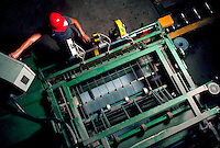 Overhead shot of worker at controls of machine at asphalt roofing factory