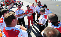 Jun. 21, 2008; Newton, IA, USA; IRL driver Helio Castroneves (center) talks with his crew during practice for the Iowa Corn Indy 250 at the Iowa Speedway. Mandatory Credit: Mark J. Rebilas-