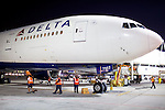 Ground crew members work after the arrival of a Delta 777 flight from Johannesburg, South Africa at Gate F8 outside of the Maynard H. Jackson Jr. International Terminal at Hartsfield–Jackson Atlanta International Airport, in Atlanta, Georgia on August 28, 2013.