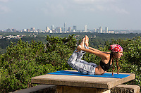 Young pretty Austin woman doing yoga exercises pose on top of Mount Bonnell overlooking the Austin, Texas skyline