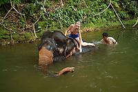 A western tourist helping an Asian elephant to take a bath.