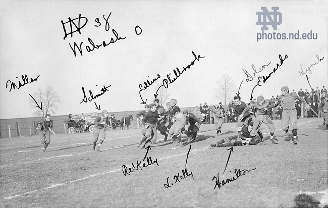 """GATH 24/17:  Football Game Scene - Notre Dame vs. Wabash, 1909/1120.  Notre Dame offensive play including Harry """"Red"""" Miller, William Schmitt, Joe Collins, George Philbrook, Al """"Red"""" Kelly, Luke Kelly, Don Hamilton, Sam """"Rosey"""" Dolan, Howard """"Cap"""" Edwards, Ed Lynch.  Image from the University of Notre Dame Archives."""