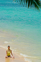 Woman meditating in lotus position on white sand beach in Hawaii