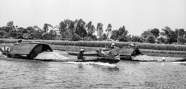 Boats transporting their goods along the Song Huong, (Perfume River) in Hue, Vietnam