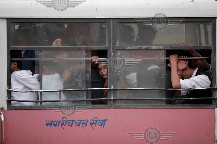 A bus crowded with students in the center of Jaipur, also called the Pink City.