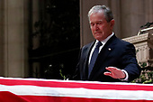 Former President George W. Bush touches the casket of his father, former President George H.W. Bush, at the State Funeral at the National Cathedral, Wednesday, Dec. 5, 2018, in Washington.<br /> Credit: Alex Brandon / Pool via CNP