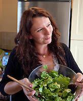 Pleased Polish woman age 32 holding a glass salad bowel of fresh greens in her kitchen. Zawady Central Poland