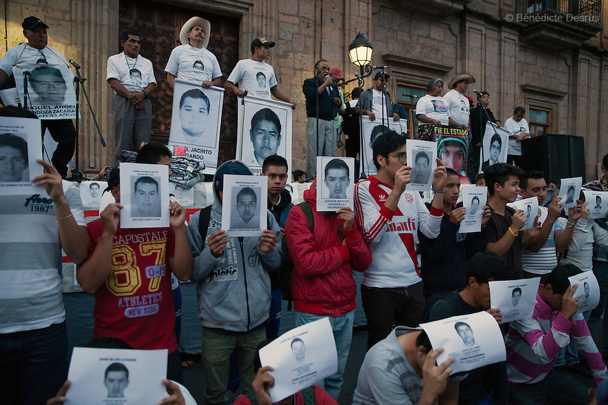 """Parents and relatives of the 43 missing students from Ayotzinapa's teacher training college, as well as classmates, hold images of the missing students and signs saying """"It was the state"""" during a march in Morelia, Michoacan, Mexico on November 19, 2014. The relatives of the 43 missing students still do not believe the official line that the young men are all dead, and with classmates, social organizations and human rights defenders, they started on Thursday a national caravan. They split up into three different caravans, branching out to share information face to face with supporters in other cities and rally nationwide support. The three groups will meet in Mexico City on Thursday 20 for a general strike and massive marches to demand justice and fight against corrupted government and organized crime. Criticism of the government has intensified in Mexico, and many are demanding that the search for the 43 missing students continue until there is concrete evidence to the contrary. (Photo by BénédicteDesrus)"""