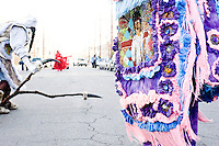 "Ruben Jones, ""flag boy"" of the Golden Comanches Mardi Gras Indians, picks up his stick en route to helping a flag boy halt traffic while another wild man displays his ornate beadwork in New Orleans on February 28, 2006."