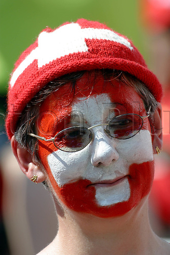 13 June 2004: A Swiss fan with her face painted before the Euro 2004 Group B game between Switzerland and Croatia at the Estadio Dr. Magalhaes Pessoa, Leiria, Portugal. Photo: Glyn Kirk/actionplus..040613 football soccer crowd fancy dress hat paint flag