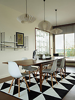 In the dining room, three pendant lights with retro style shades hang above a wood dining table; the dining chairs are Eames shell chairs with Eiffel Tower base; a few items are displayed on a simple, wall-mounted shelving unit.  An Ikea rug echoes the geometric motif found throughout the apartment and the overall retro feel chimes with the Bauhaus design of the building.
