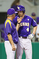 LSU Tigers outfielder Raph Rhymes #4 talks with coach Paul Mainieri during the game against the Auburn Tigers in the NCAA baseball game on March 23, 2013 at Alex Box Stadium in Baton Rouge, Louisiana. LSU defeated Auburn 5-1. (Andrew Woolley/Four Seam Images).