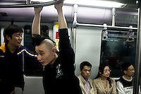 Duwei, drummer for the Nanjing-based punk band Overdose, rides the subway in Shanghai, China, between gigs.