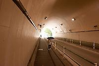 Daytime landscape view of a woman walking with an open umbrella in underground passageway near Kamiyacho Eki following the 311 Tohoku Tsunami in Tokyo, Japan  © LAN