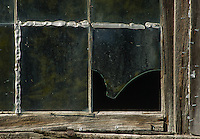 An old barn sports a broken window and remnents of quick fixes of stapled plastic, Door County, Wisconsin
