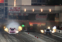 Oct. 27, 2012; Las Vegas, NV, USA: NHRA funny car driver Tony Pedregon (right) races alongside Courtney Force during qualifying for the Big O Tires Nationals at The Strip in Las Vegas. Mandatory Credit: Mark J. Rebilas-