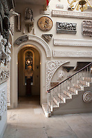 The walls of the stately staircase hall display a collecton of bas reliefs and sculpture