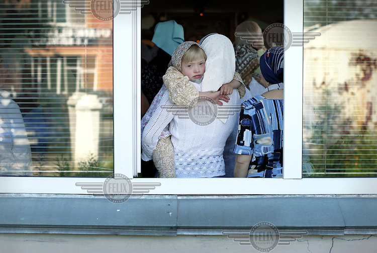 A woman and her daughter attend a church service at a Russian Orthodox church in Abakan.