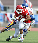 SIOUX FALLS, SD - SEPTEMBER 7:  Caden Quintanilla #25 from Lincoln is grabbed from behind by Isaac Althoff #42 from O'Gorman in the first quarter of their game at the 2013 Presidents Bowl at Howard Wood Field. (Photo by Dave Eggen/Inertia)